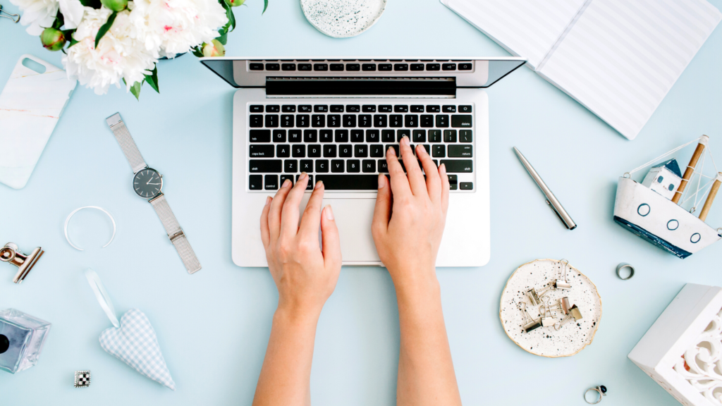 Marketer using laptop on blue desk